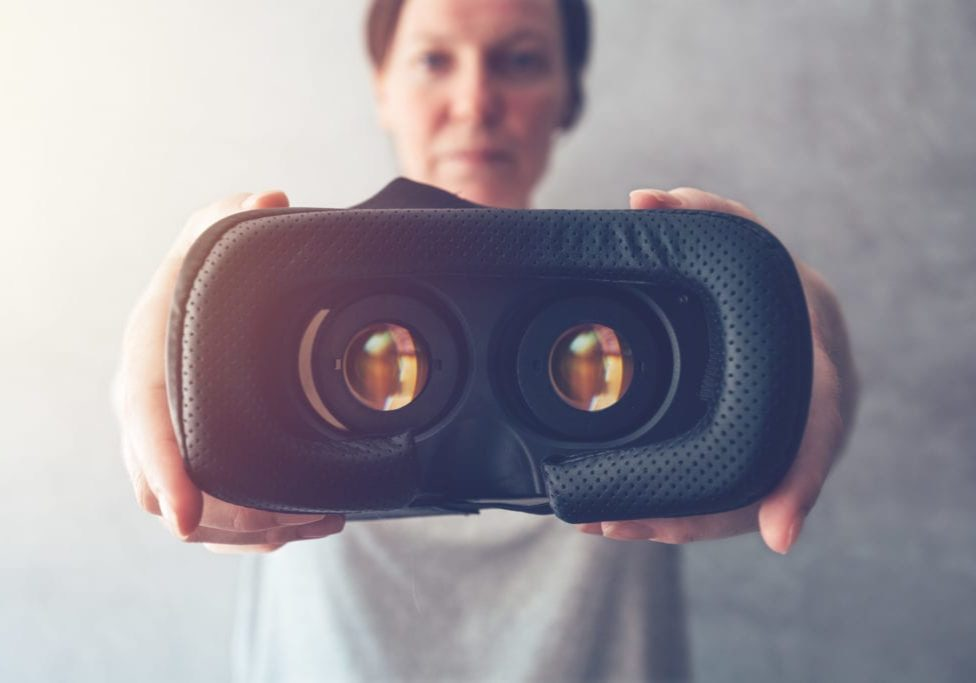 Woman offering VR headset, modern device for virtual reality immersion, selective focus
